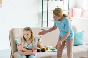 An angry mother yelling while standing over her teen daughter.