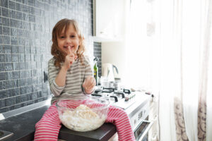 Five years old child cooking in the kitchen