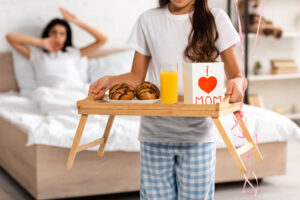 cropped view of child holding tray with breakfast, mothers day card with heart sign and mom lettering, while mother stretching in bed