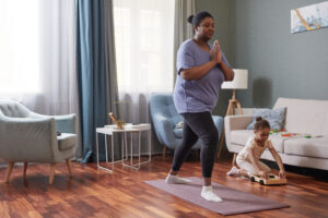 Full length portrait of African-American woman doing yoga at home with little girl in background