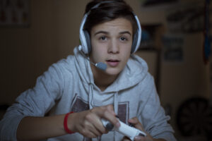 Teenage boy with headset playing video game
