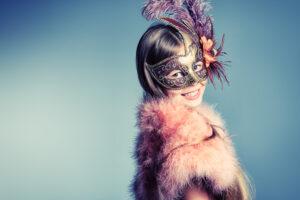 Girl in festive dress and carnival mask posing