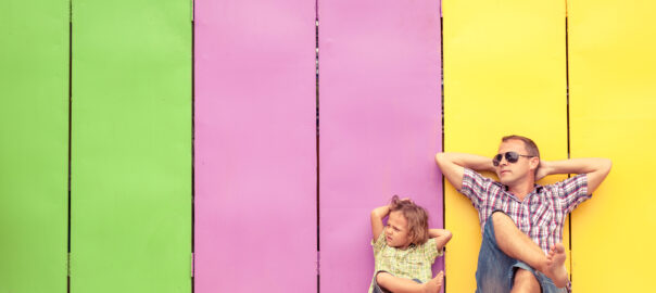 Father and son relaxing in front of a colorful house